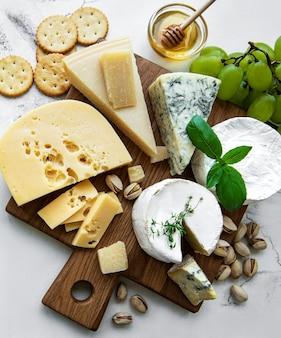 Diverse soorten kaas, druiven en honing op een marmeren ondergrond