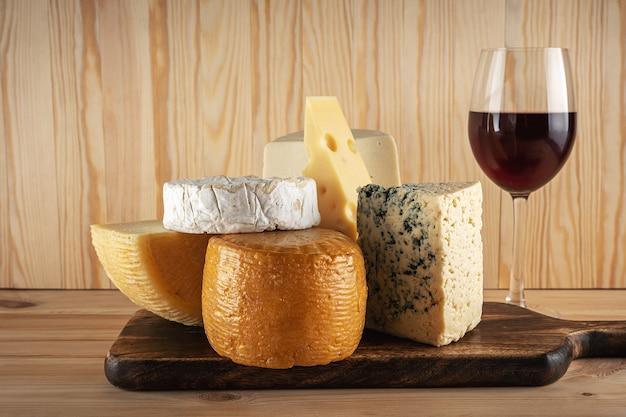 Diverse soorten kaas met glas wijn op houten tafel.
