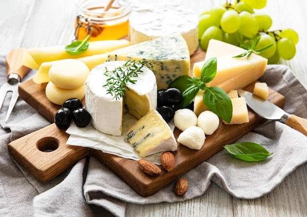 Diverse soorten kaas op een witte houten achtergrond
