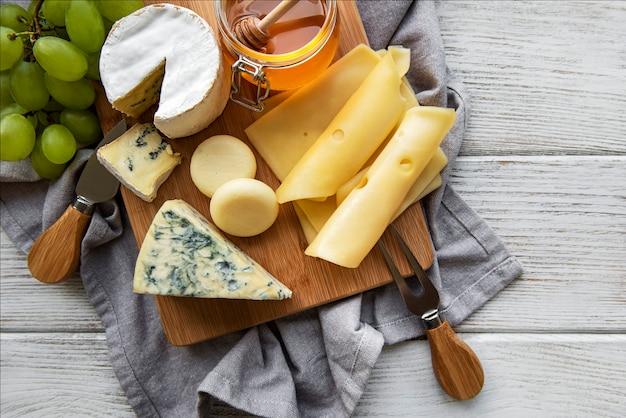Diverse soorten kaas op een witte houten ondergrond