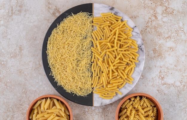 Diverse soorten ongekookte macaroni op een mooi bord