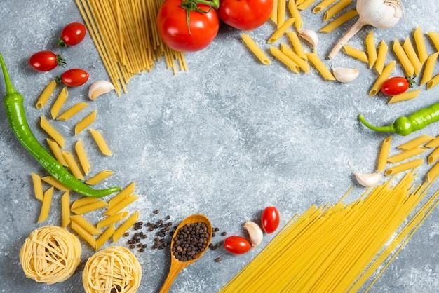 Diverse soorten ongekookte spaghetti met groenten
