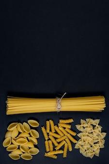 Diverse soorten pasta op zwarte achtergrond. bovenaanzicht. diverse soorten pasta. kopieer ruimte voor ontwerp.