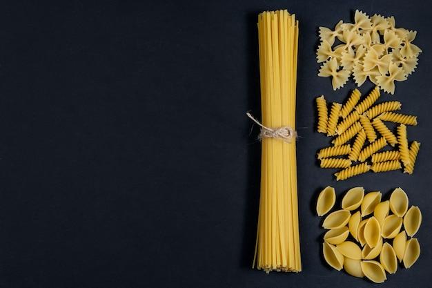 Diverse soorten pasta op zwarte achtergrond. bovenaanzicht. diverse vormen van pasta. kopieer ruimte voor ontwerp.