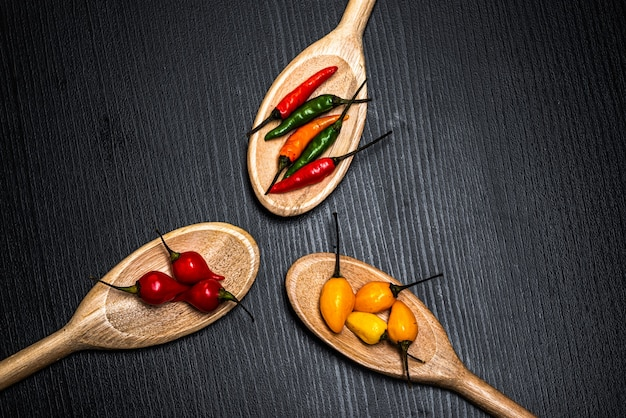 Diverse soorten pepers chilipepers peperbolletjes en cumary peper van para¡ in houten lepels op...