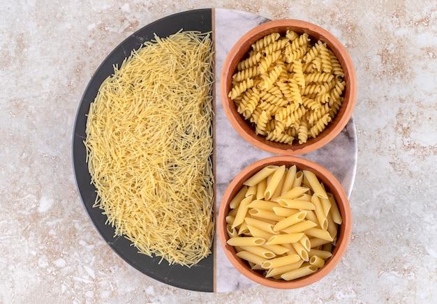 Diverse soorten rauwe pasta op een marmeren ondergrond