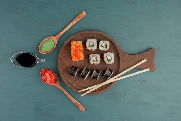 Diverse soorten sushi roll plaat met ingelegde gember, wasabi en sojasaus op blauwe tafel.