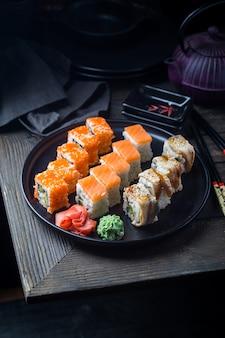 Diverse soorten sushibroodjes die op zwarte plaat over donker worden gediend
