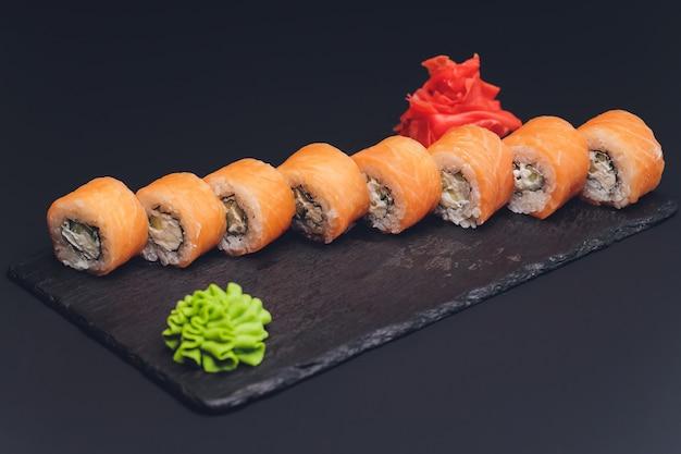 Diverse soorten sushivoedsel dat op zwarte achtergrond wordt gediend.