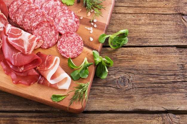 Diverse soorten vlees en worst op houten tafel