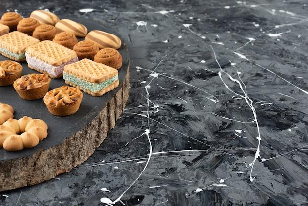 Diverse soorten zoete gebakjes op een houten stuk.