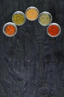 Diverse specerijen en kruiden in een transparante kom op zwarte houten achtergrond, bovenaanzicht met tekst kopiëren.