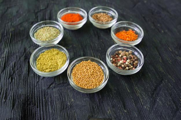 Diverse specerijen en kruiden in een transparante kom op zwarte houten ondergrond, close-up.
