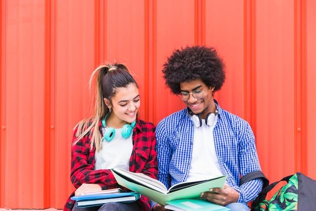 Diverse studenten die samen tegen een oranje achtergrond bestuderen