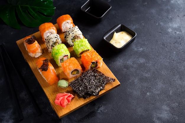 Diverse sushi die op houten plaat met leistokken, saus en nori op zwarte worden geplaatst