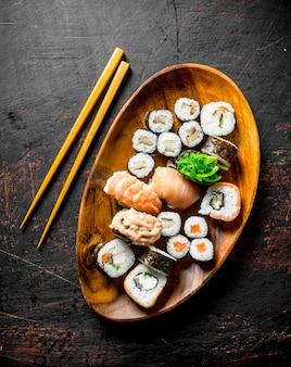 Diverse sushi en broodjes op een bord met stokken. op donkere rustieke ondergrond