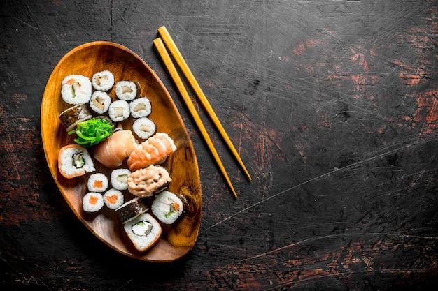 Diverse sushi en broodjes op een bord met stokken.