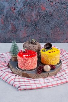Diverse taarten op donker bord met kerstversieringen.