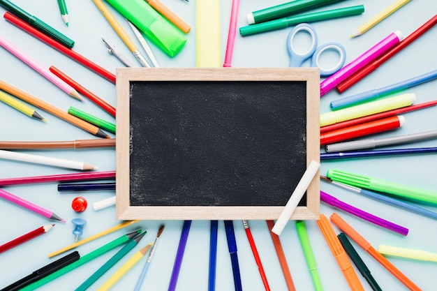 Diverse tekenhulpmiddelen die rond leeg bord op blauw bureau worden verspreid