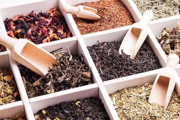 Diverse thee in een houten kist en bolletjes