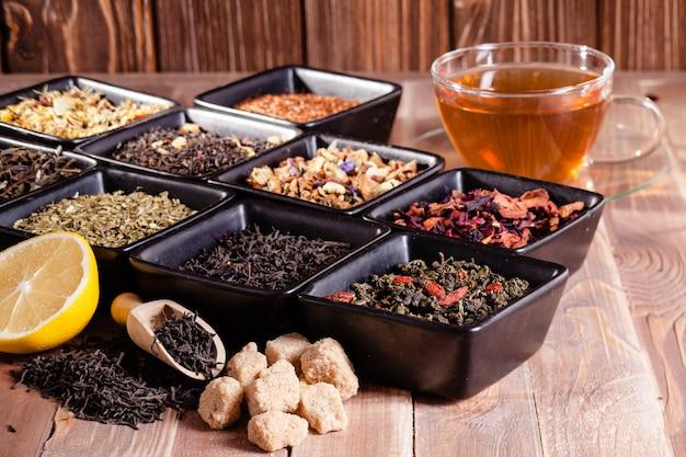 Diverse thee in zwarte keramische kommen en een kopje met warme drank