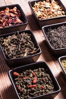 Diverse thee in zwarte keramische kommen op een houten tafel