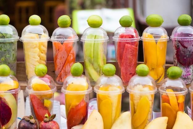 Diverse tropische vruchten, bereid in kopjes voor het maken van smoothies met gemengde vruchten, wachtend op klanten