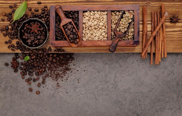 Diverse van gebrande koffiebonen in houten kist met handmatige koffiemolen setup op armoedige houten.