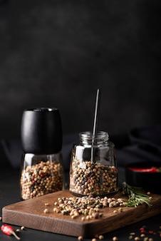 Diverse verschillende soorten piment in een glazen pot op een houten bord