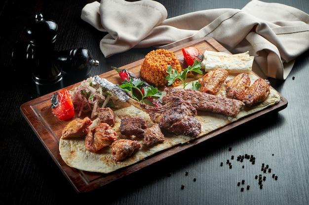 Diverse verschillende soorten vlees gebakken boven het vuur. spiesjes van rundvlees, kip, varkensvlees, lamsvlees en kebab met rijst en groenten garneren. sish kebab