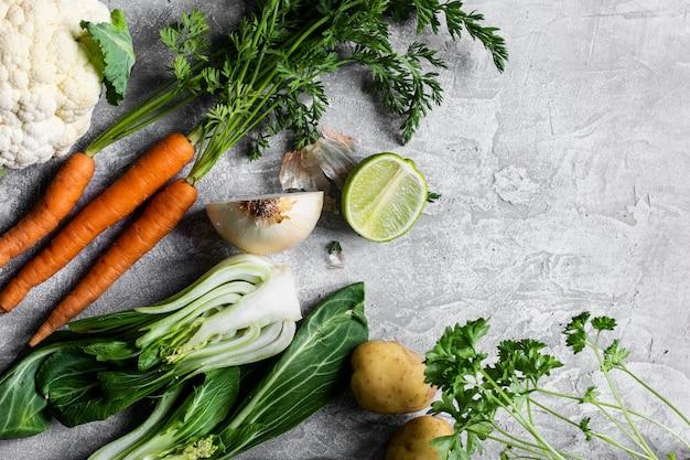 Diverse verse biologische groenten op een grijs keukenblad