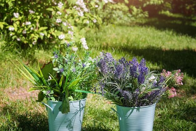 Diverse verse bloemen arrangement in metalen emmers in de tuin. decoratieve boeketten voor een feestelijk evenement.