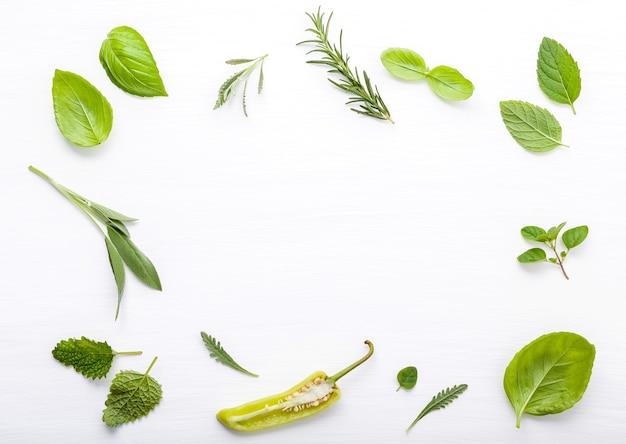 Diverse verse kruiden voor het koken van ingrediens op witte houten achtergrond met vlakte leggen.