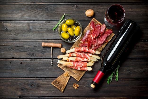 Diverse vlees voorgerecht met olijven, jamon en rode wijn op een rustieke tafel.