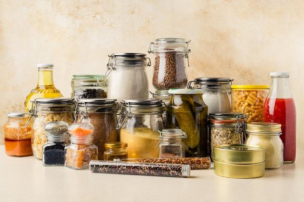 Diverse voedselvoorraden waaronder granen, specerijen, tomatensaus, olie in glazen containers, ingeblikte producten