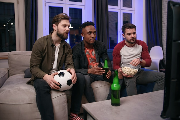 Diverse voetbalfans die voor favoriet team toejuichen en thuis bier drinken, exemplaarruimte