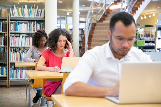 Diverse volwassen studenten die aan computer in klaslokaal werken