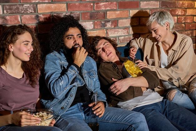 Diverse vrienden die tv kijken terwijl verveelde vriend thuis in de woonkamer slaapt, in slaap valt tijdens film, woninginrichting