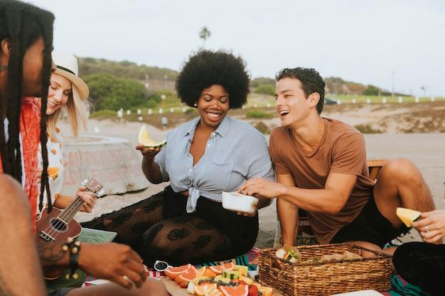 Diverse vrienden die van een strandpartij genieten