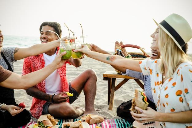 Diverse vrienden die van een strandpicknick genieten