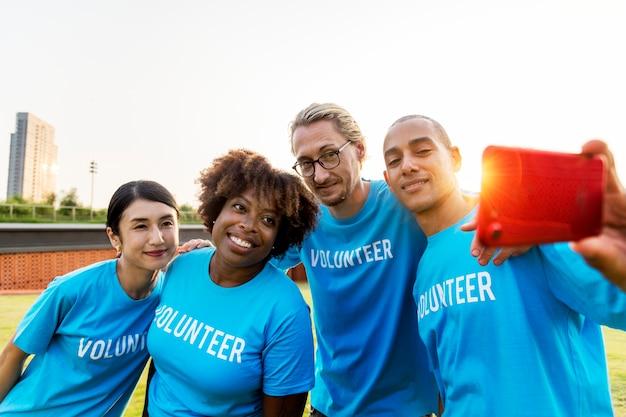Diverse vrijwilligers die samen een selfie maken