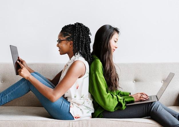 Diverse vrouwen die bij elkaar zitten met behulp van digitale apparaten