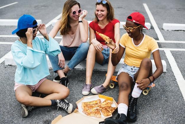 Diverse vrouwen die op vloer zitten die pizza samen eten