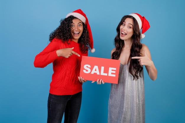 Diverse vrouwen die santahoeden met rood verkoopteken dragen