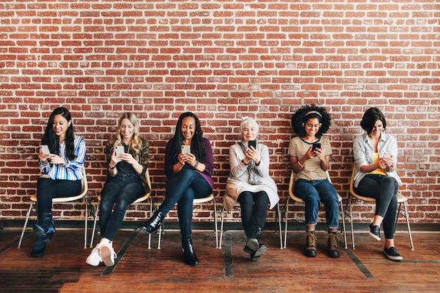 Diverse vrouwen die zich concentreren op hun telefoons