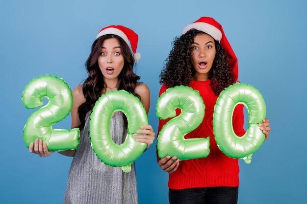 Diverse vrouwen met 2020 nieuwe jaarballons die geïsoleerde kerstmishoeden dragen