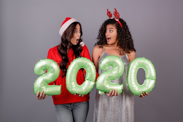 Diverse vrouwen met 2020 nieuwe jaarballons die kerstmishoed dragen die over grijs wordt geïsoleerd