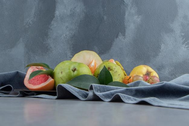 Diverse vruchten gebundeld op een stuk stof op marmer