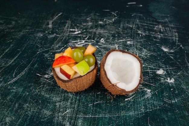 Diverse vruchten in half gesneden kokosnoot op marmeren tafel.