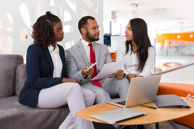 Diverse zakelijke collega's bestuderen overeenkomst